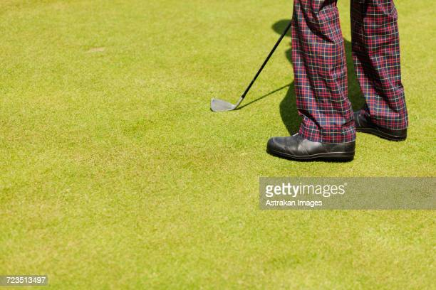 Low section of man with golf club on field