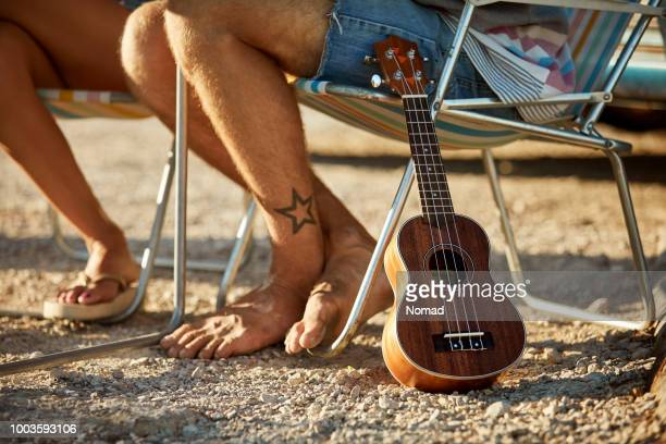 low section of man with guitar on cliff - stars and strings stock photos and pictures