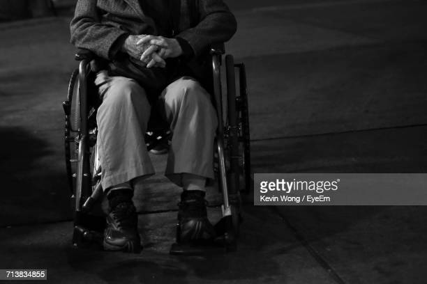 Low Section Of Man With Hands Clasped Sitting On Wheelchair