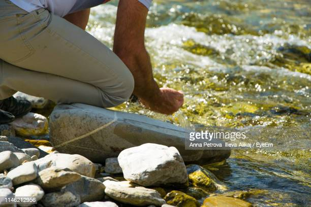 low section of man with hands cupped by river - geología fotografías e imágenes de stock