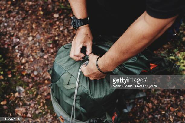 low section of man with luggage in forest during autumn - low section stock pictures, royalty-free photos & images