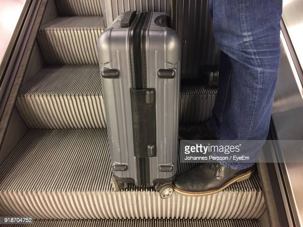 Low Section Of Man With Luggage Standing On Escalator