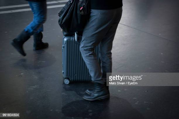 Low Section Of Man With Luggage Standing On Floor