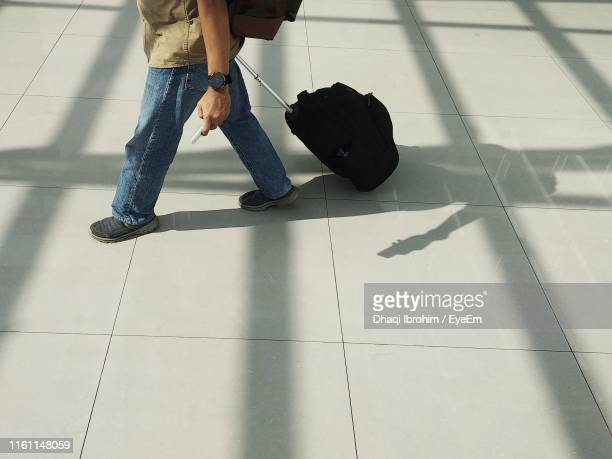 Low Section Of Man With Luggage Walking On Tiled Floor