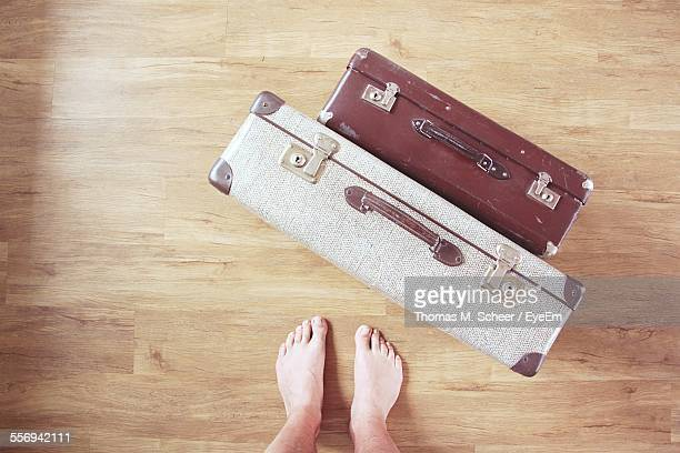 Low Section Of Man With Old-Fashioned Suitcases On Hardwood Floor