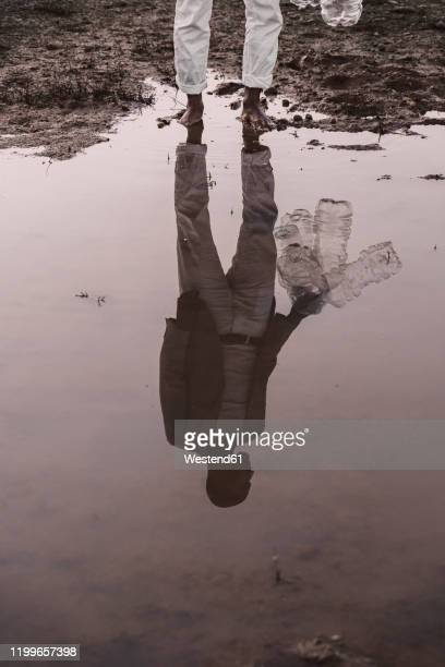 low section of man with plastic bottles standing at water hole - waterhole stock pictures, royalty-free photos & images
