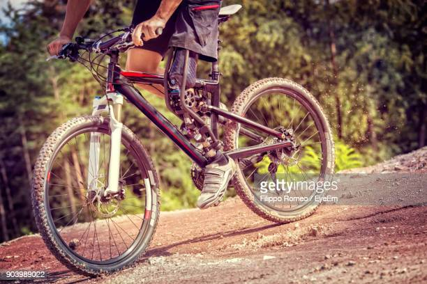 Low Section Of Man With Prosthetic Leg Riding Bicycle On Field