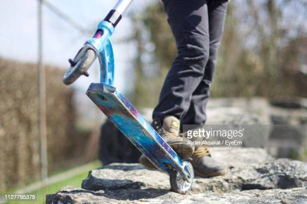 Low Section Of Man With Push Scooter On Wall