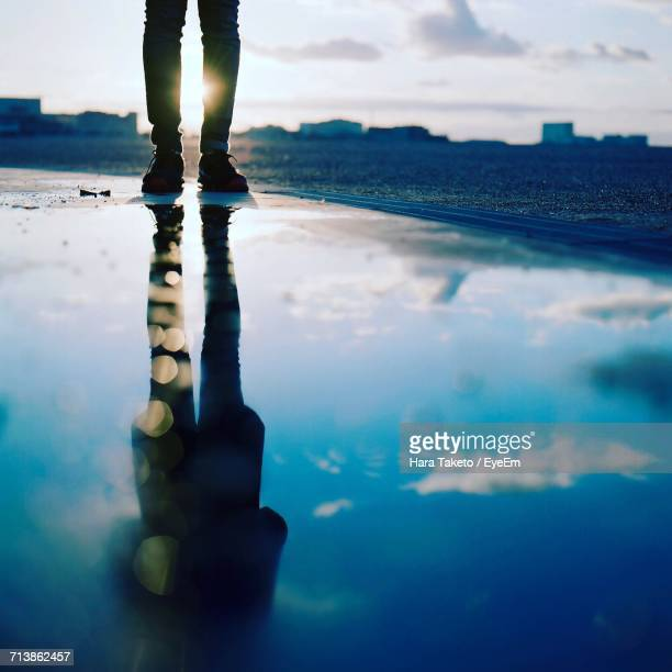 Low Section Of Man With Reflection In Water