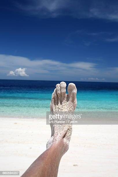 low section of man with sand at beach against blue sky during sunny day - beautiful male feet stock photos and pictures