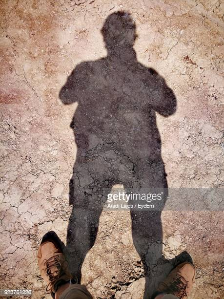 Low Section Of Man With Shadow Standing On Sand