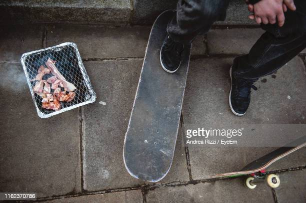 low section of man with skateboard by meat on footpath - andrea rizzi - fotografias e filmes do acervo