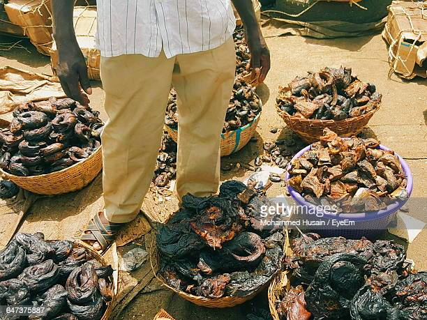 low section of man with smoked fish for sale at market - nigerian food stock pictures, royalty-free photos & images