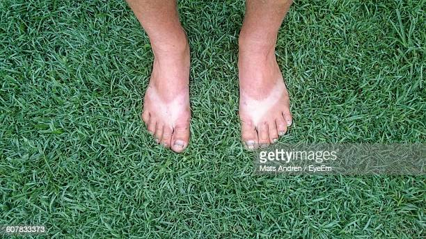 low section of man with tan lines standing on grassy field - marque de bronzage photos et images de collection