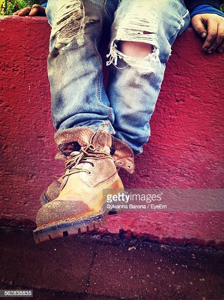 Low Section Of Man With Torn Jeans And Dirty Shoes