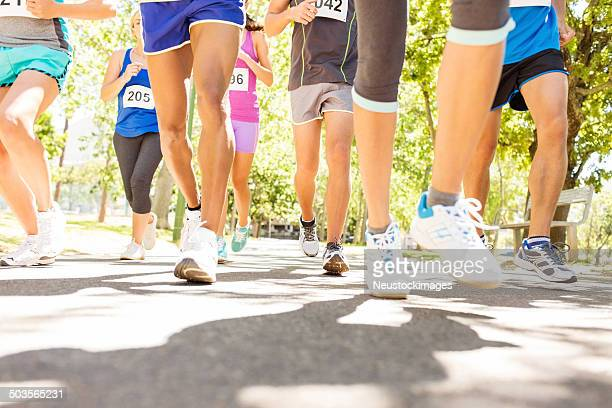 low section of marathon runners competing at park - charity benefit stock pictures, royalty-free photos & images