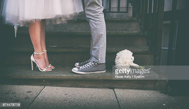 Low Section Of Married Couple With White Bouquet