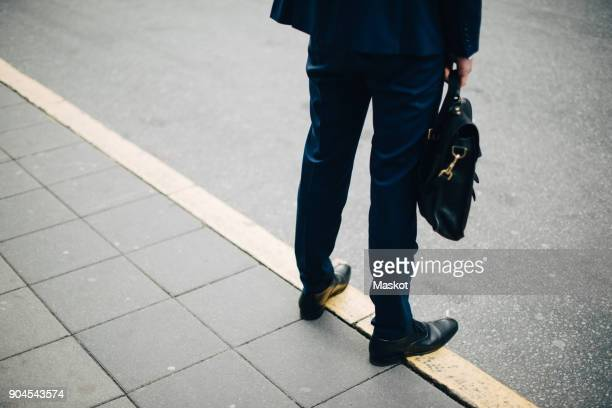 Low section of mature businessman with bag standing on sidewalk in city