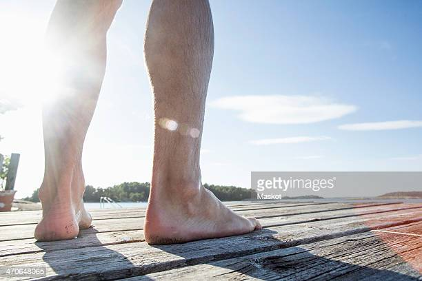 Low section of mature man standing on boardwalk