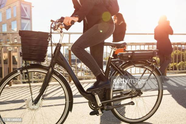 low section of mature woman riding electric bicycle by commuters on bridge in city against sky - tvåhjulig cykel bildbanksfoton och bilder
