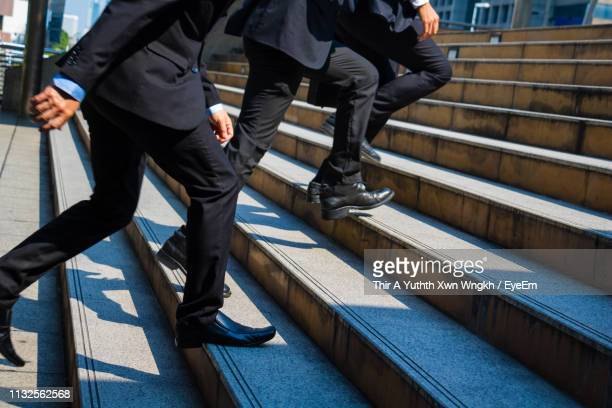 low section of men moving up on steps in city - human foot stock pictures, royalty-free photos & images
