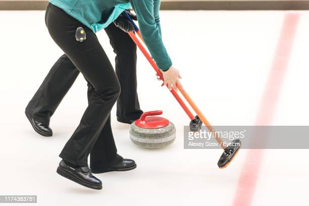 low section of men playing curling on ice rink - カーリング ストックフォトと画像