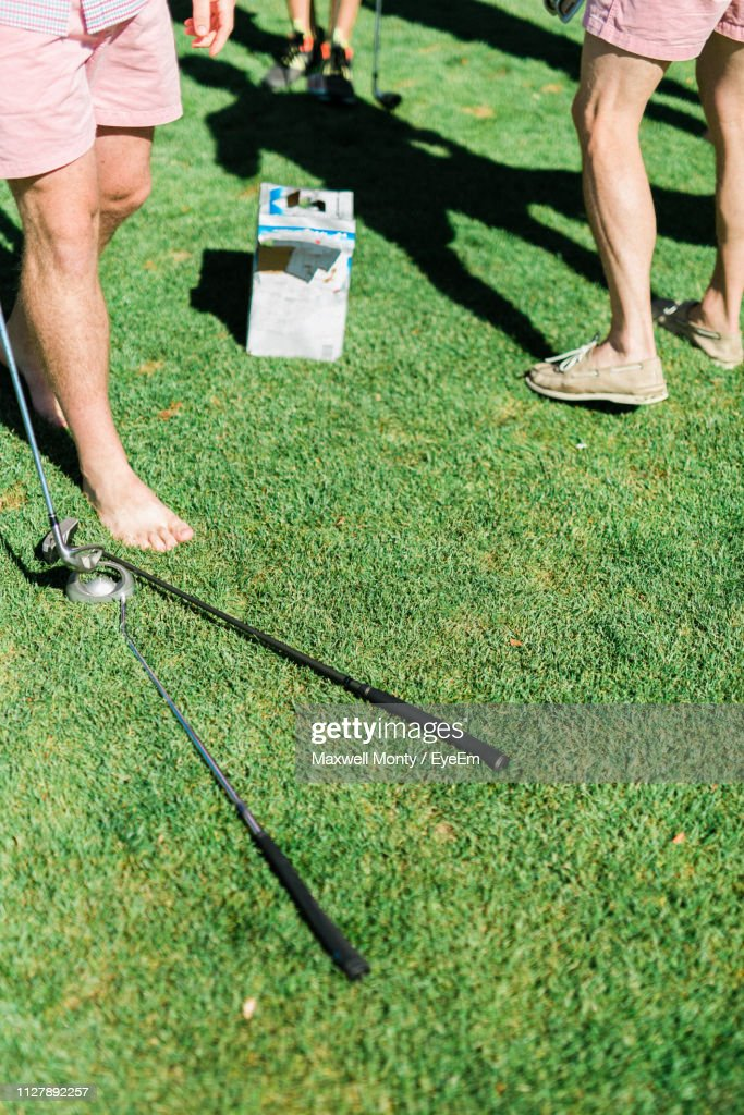 Low Section Of Men Playing Golf On Grassy Field During Sunny Day : Stock Photo