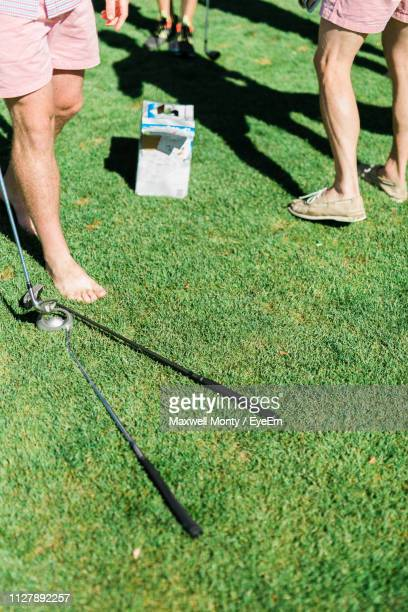 low section of men playing golf on grassy field during sunny day - monty shadow stock photos and pictures