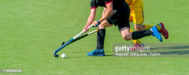 low section of men playing hockey - cetkauskas stock pictures, royalty-free photos & images