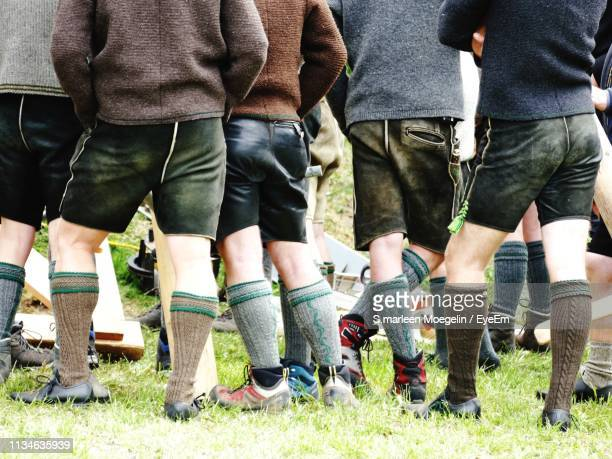 low section of men standing on grassy field - tegernsee stock pictures, royalty-free photos & images