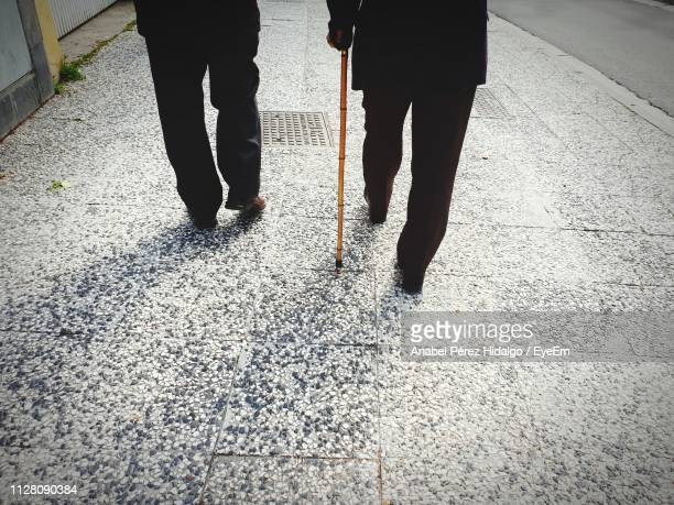 low section of men walking on sidewalk - 杖 ストックフォトと画像