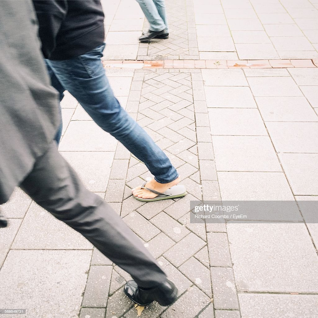 Low Section Of Men Walking On Street : Stock Photo