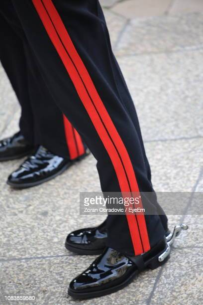 Low Section Of Men Wearing Black Shoes And Pants Standing On Footpath
