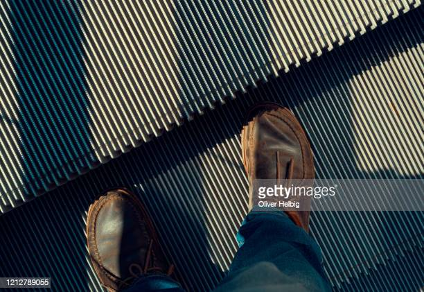 low section of men wearing brown casual leather shoes standing on escalator - マゾフシェ県 ストックフォトと画像