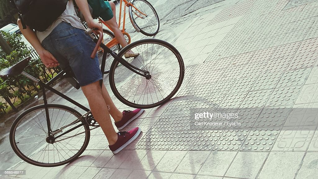 Low Section Of Men With Bicycle : Stock Photo