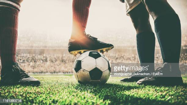 low section of men with soccer ball on field - fußball stock-fotos und bilder