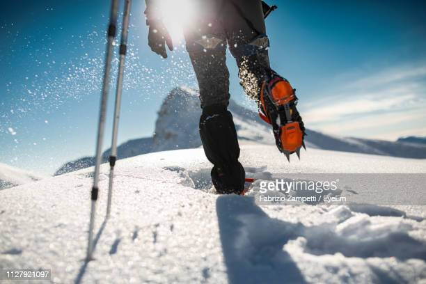 Low Section Of Mid Adult Man Hiking On Snow Covered Mountain Against Sky During Sunny Day