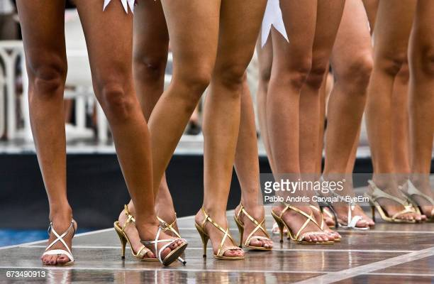 low section of models wearing high heels while standing in fashion show - leg show stock pictures, royalty-free photos & images