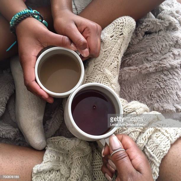 Low Section Of Mother And Daughter Holding Coffee Cups During Winter