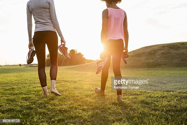 low section of mother and daughter holding sports shoes while walking on grass at park during sunset - low section stock pictures, royalty-free photos & images