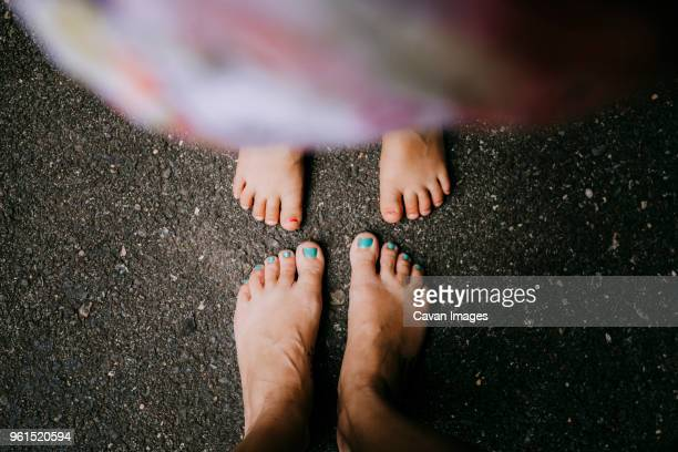 Low section of mother and daughter standing on asphalt
