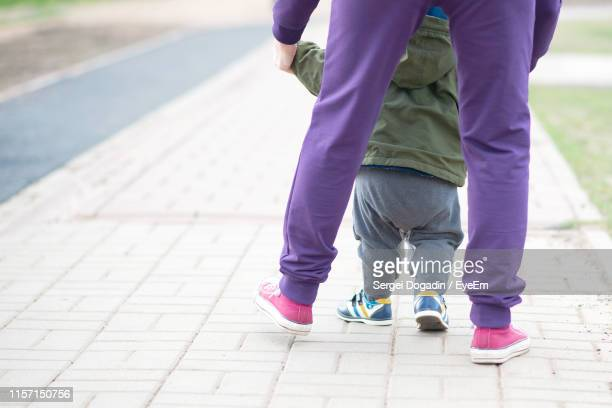 low section of mother and son walking on footpath - purple shoe stock pictures, royalty-free photos & images