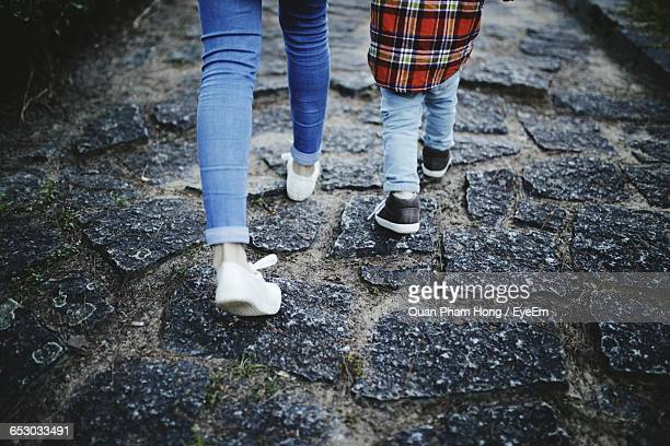 low section of mother and son walking on walkway - hong quan stock pictures, royalty-free photos & images