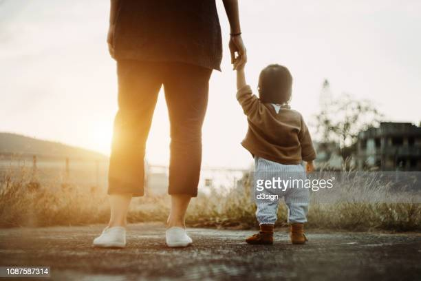 low section of mother holding baby daughter's hand  walking in the park and enjoying the beautiful sunset - besonderes lebensereignis stock-fotos und bilder