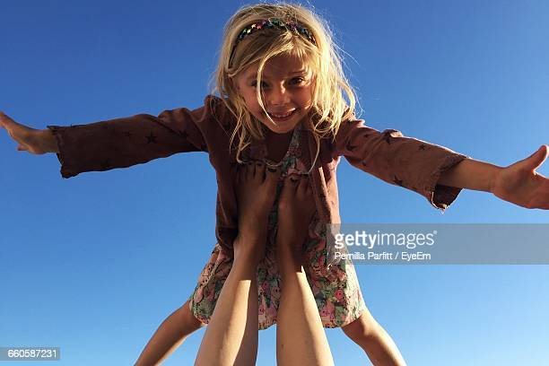 Low Section Of Mother Legs Balancing Happy Daughter Against Clear Blue Sky