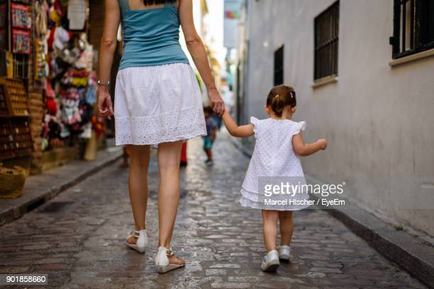 low section of mother walking with daughter on street - parte inferior imagens e fotografias de stock