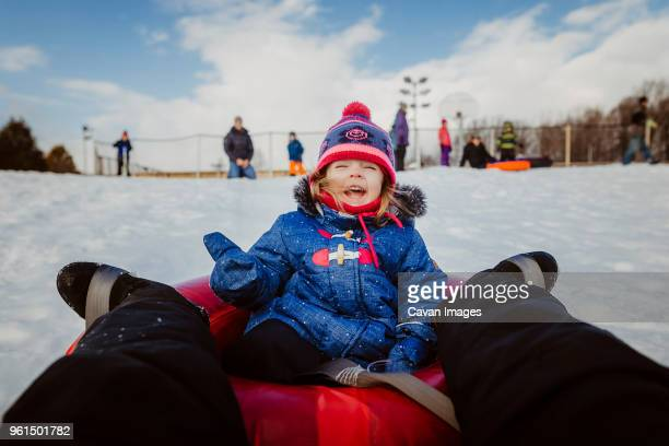 low section of mother with daughter tobogganing on snow covered field against cloudy sky - tobogganing stock pictures, royalty-free photos & images