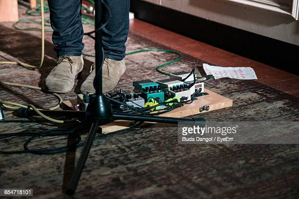 Low Section Of Musician Standing By Guitar Effects Pedal On Floor