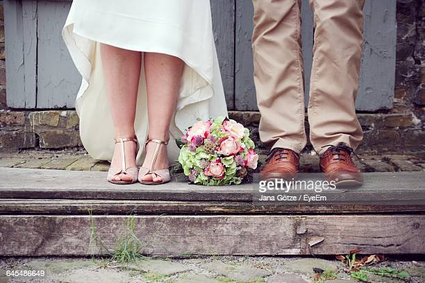 Low Section Of Newlywed Couple Standing By Door