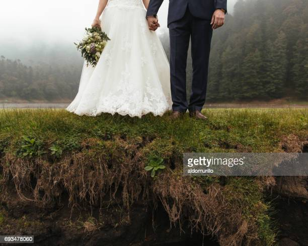Low section of newlyweds standing on edge and holding hands